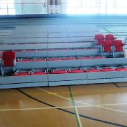 Retractable auditorium seating comprising: Eight rows of 10 upholstered fold-up seating, approx.
