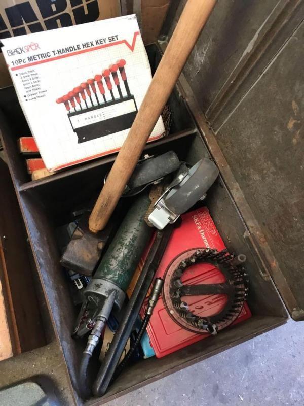 Metallbox mit Bohrern, neuen Stilsons, Schleifsteinen und einem Vorschlaghammer